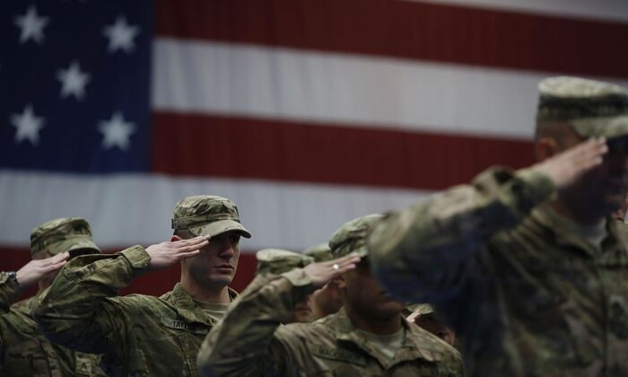 Soldiers from the U.S. Army's 3rd Brigade Combat Team, 1st Infantry Division, salute during the playing of the Star-Spangled Banner during a homecoming ceremony in the Natcher Physical Fitness Center in Fort Knox, Kentucky on Feb. 27, 2014. (Luke Sharrett/Getty Images)