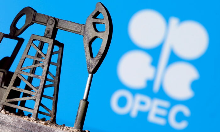 A 3D printed oil pump jack is seen in front of displayed OPEC logo in this illustration picture on April 14, 2020. (Dado Ruvic/Illustration/Reuters)