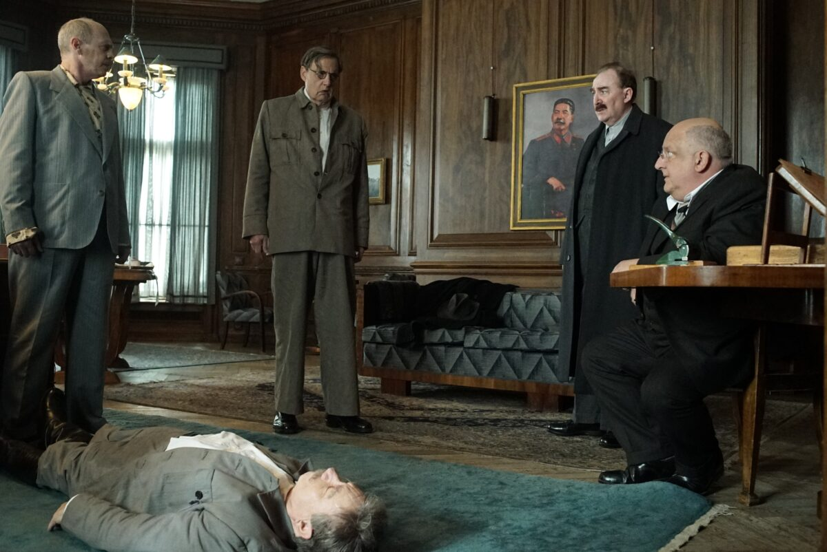 four men stand around dead body in The Death of Stalin