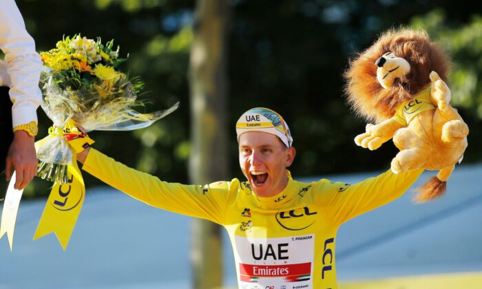UAE Team Emirates rider Tadej Pogacar of Slovenia celebrates on the podium after winning the yellow jersey and the Tour de France, Cycling, in France, on July 18, 2021. (Stephane Mahe/Reuters)