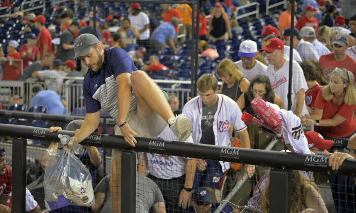 Fans pour out onto the field after hearing gunfire from outside the stadium, during a baseball game between the San Diego Padres and the Washington Nationals at Nationals Park in Washington on July 17, 2021. (John McDonnell/The Washington Post via AP)
