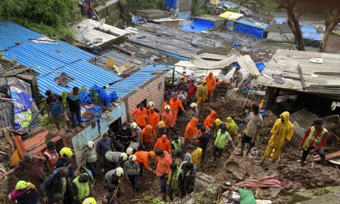 Rescuers look for survivors after a wall collapsed on several slum houses heavy monsoon rains in the Mahul area of Mumbai, India, on July 18, 2021. (Rajanish Kakade/AP Photo)