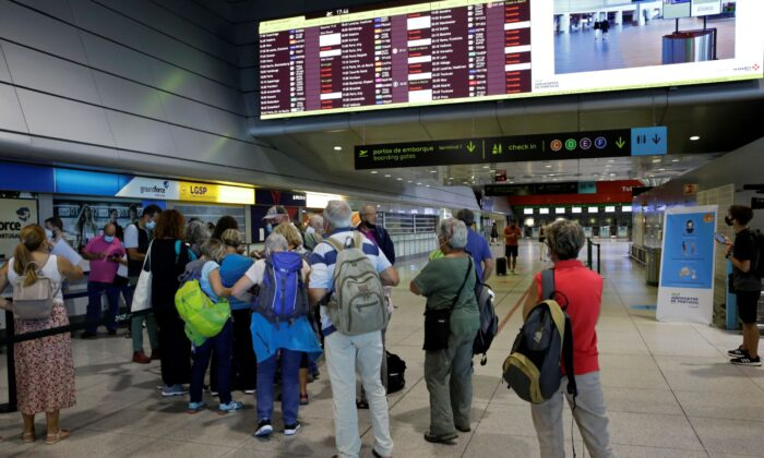 Passengers queue at the counter of Groundforce, a ground handling company at Lisbon airport, beneath a screen showing departing flights, Portugal, on July 17, 2021. (Armando Franca/AP Photo)
