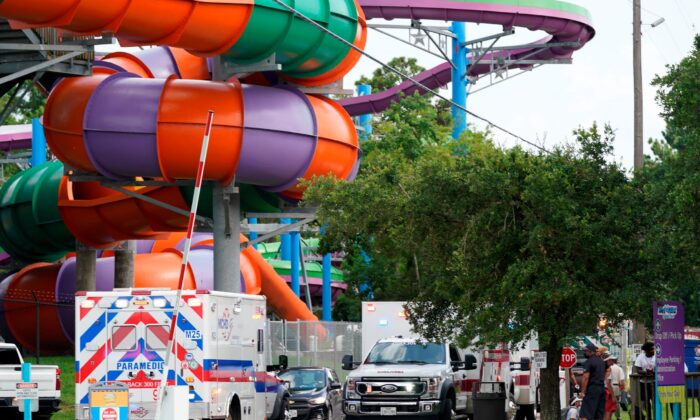 Emergency personnel vehicles are parked near the scene where people are being treated after chemical leak at Six Flags Hurricane Harbor Splashtown, in Spring, Texas, on July 17, 2021. (Melissa Phillip/Houston Chronicle via AP)
