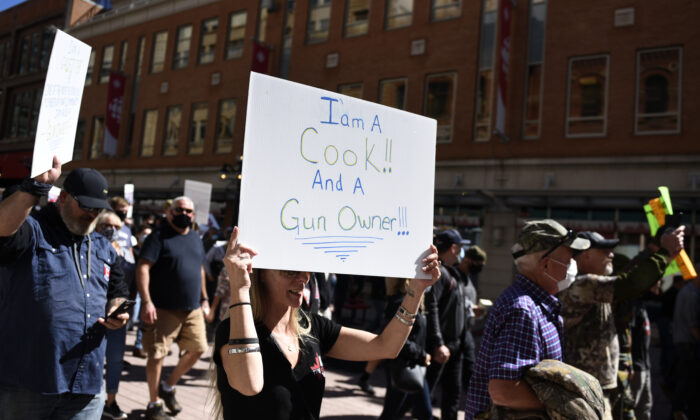 Gun owners hold signs as they participate in a rally organized by the Canadian Coalition for Firearm Rights against the government's new gun regulations, in Ottawa on Sept. 12, 2020. (THE CANADIAN PRESS/Justin Tang)