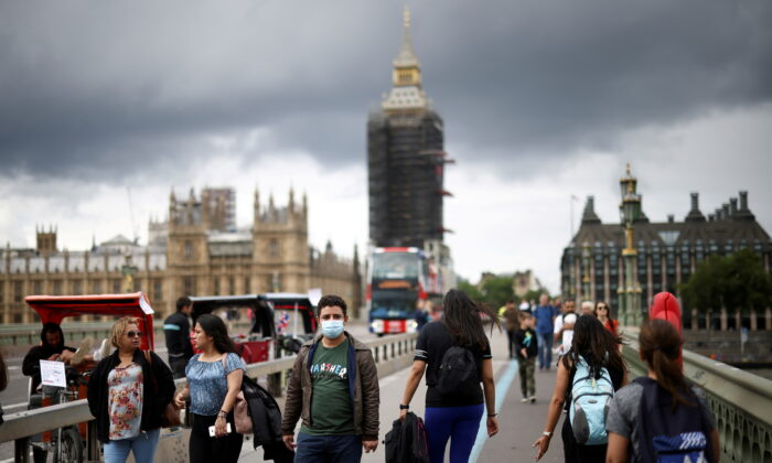 People, some wearing protective masks, walk over Westminster Bridge, amid the COVID-19 pandemic, in London on July 4, 2021. (Henry Nicholls/Reuters)