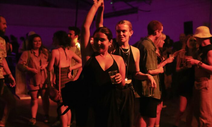 """Revellers dance during the """"00:01"""" event organised by Egyptian Elbows at Oval Space nightclub, as England lifted most COVID-19 restrictions at midnight, in London, early July 19, 2021. (Natalie Thomas/Reuters)"""