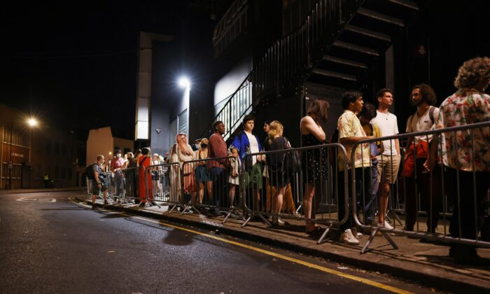 """People arrive for the """"00:01"""" event organised by Egyptian Elbows at Oval Space nightclub, as England lifted most CCP virus disease (COVID-19) restrictions at midnight, in London on July 19, 2021. (Natalie Thomas/Reuters)"""