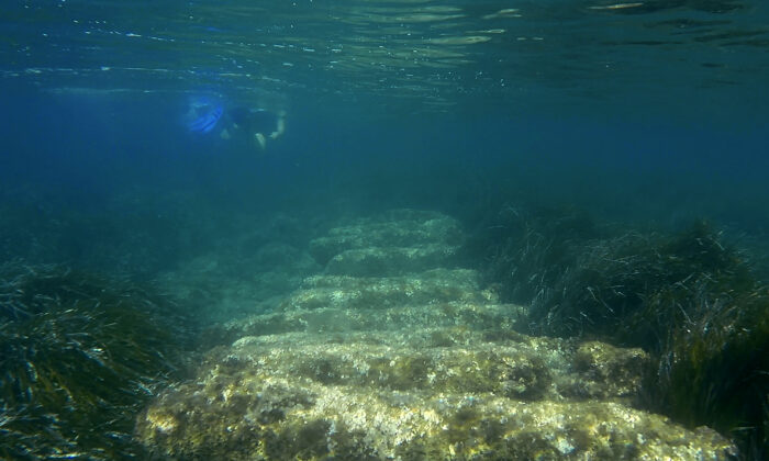 Cyprus Antiquities Department official Yiannis Violaris snorkels over submerged stone remains of the ancient harbor next of Amathus ancient city, in the eastern Mediterranean island of Cyprus, on July 1, 2021. (Petros Karadjias/AP Photo)