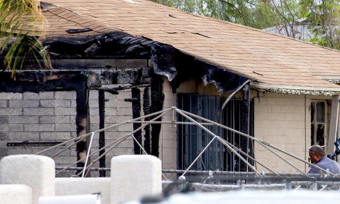 Tucson Police investigators work at the scene of a house fire where a body was found in Tucson, Ariz., on July 19, 2021. (Rebecca Sasnett/Arizona Daily Star via AP)