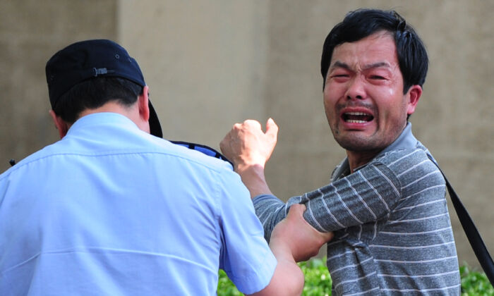 A police officer is detaining a petitioner, who is protesting about medical and land grab issues, outside the Chaoyang Hospital in Beijing, China on May 8, 2012. (Mark Ralston/AFP/Getty Images)