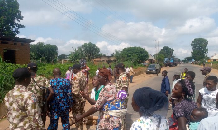 Women and children demand withdrawal of military after alleged shooting of two civilians, in conflict Zone south of Jos, Nigeria, on July 14, 2021.  Protestors tell Military Officials who visit protest ground that they no longer trust Army to protect them.  Masara Kim