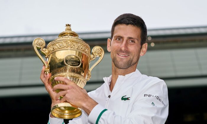 Novak Djokovic of Serbia holds the trophy after beating Matteo Berrettini of Italy in the men's final on Centre Court at The Wimbledon Tennis Championships in London on July 11, 2021. (Peter van den Berg/USA TODAY Sports via Reuters)