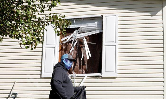 A person cleans up debris from a broken window at a home FBI agents searched in Hartland Township mobile home in connection of a plot to kidnap Michigan Gov. Gretchen Whitmer,, in Heartland, Mich., on Oct. 8, 2020. (Jeff Kowalsky/AFP via Getty Images)