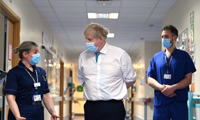 Prime Minister Boris Johnson (centre) speaks with Emma Sweeney, associate director of nursing surgery, during a visit to Colchester Hospital in Essex, Britain, on May 27, 2021. (Glyn Kirk/PA)