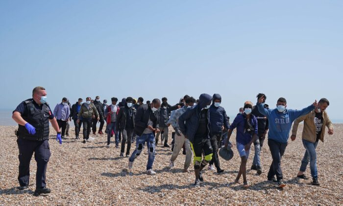 A group of people thought to be migrants are escorted by Border Force officers following a small boat incident in the Channel, from the beach in Dungeness, Kent, Britain, on July 20, 2021. (Gareth Fuller/PA)