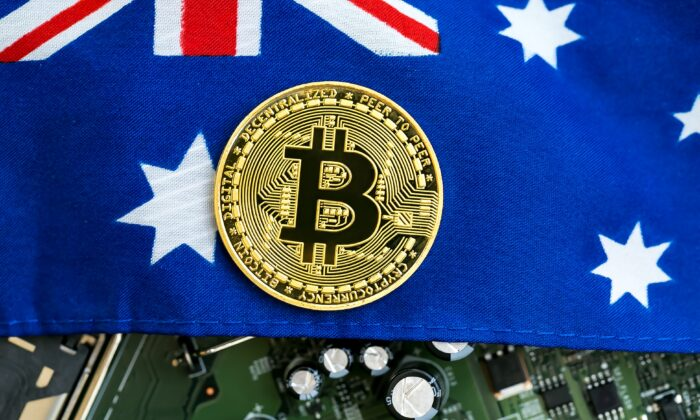A Bitcoin cryptocurrency symbol over an Australian flag and electronic components. (Tierney / Adobe Stock)