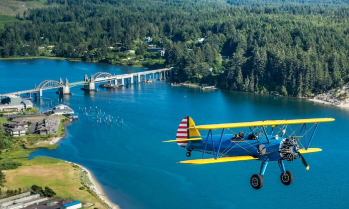 """Terry and Winette Tomeny fly pass the majestic Siuslaw River Bridge in Florence, Oregon, in their legendary Stearman """"Kaydet."""" The aircraft was the primary trainer for the U.S. Army Air Corps in World War II and is arguably the most famous biplane ever made. Tomeny Aero offers tours and flight lessons. In 2017 the Tomenys and retired airline captain Sam Spayd opened the Florence Aviation Academy, working with The Boys and Girls Club to inspire the next generation of pilots and engineers. (Courtesy of Tomeny Aero Inc)"""