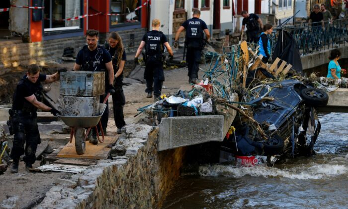 Police officers and volunteers clean rubble in an area affected by floods caused by heavy rainfalls in Bad Muenstereifel, Germany, on July 18, 2021. (REUTERS/Thilo Schmuelgen)