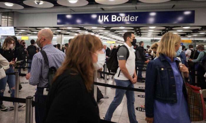 Arriving passengers queue at UK Border Control at the Terminal 5 at Heathrow Airport in London on June 29, 2021. (Hannah Mckay/Reuters)