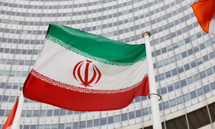 The Iranian flag waves in front of the International Atomic Energy Agency (IAEA) headquarters in Vienna, Austria, on May 23, 2021. (Leonhard Foeger/Reuters)