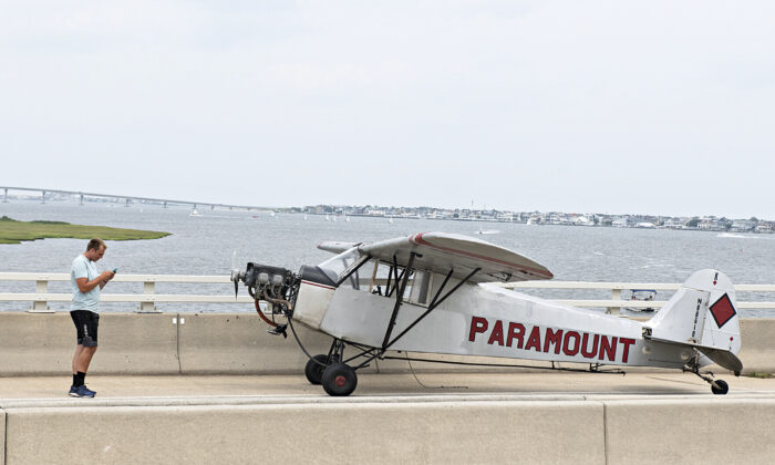 Landon Lucas stands next to his plane after he made an emergency landing on the Route 52 causeway connecting Ocean City and Somers Point, N.J., on July 19, 2021. (Matthew Strabuk/The Press of Atlantic City via AP)