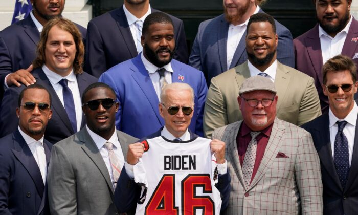 President Joe Biden, surrounded by members of the Tampa Bay Buccaneers, poses for a photo holding a jersey during a ceremony on the South Lawn of the White House, where Biden honored the Super Bowl Champion Tampa Bay Buccaneers for their Super Bowl LV victory, in Washington on July 20, 2021. (Andrew Harnik/AP Photo)