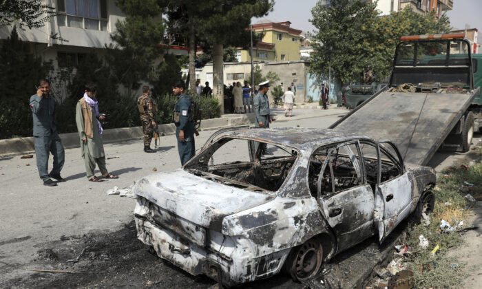 Security personnel inspect a damaged vehicle where rockets were fired from in Kabul, Afghanistan, on July 20, 2021. (Rahmat Gul/AP Photo)