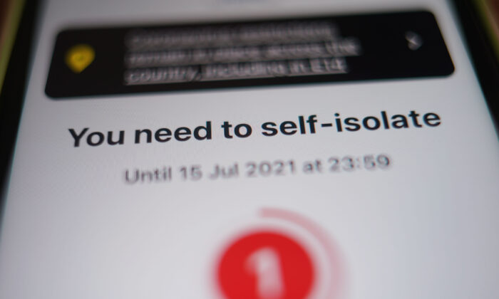 A message to self-isolate, with one day of required isolation remaining, is displayed on the NHS contact tracing app on a mobile phone, in London on July 15, 2021. (Yui Mok/PA)