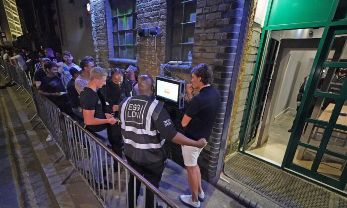 People have their ID checked as they queue up for the Egg nightclub in London, on July 19, 2021. (Jonathan Brady/PA)