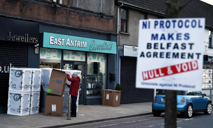 A man sorts through a delivery of washing machines with a sign is seen across the road featuring a message against the Brexit border checks in relation to the Northern Ireland protocol in the town centre of Larne, Northern Ireland, on Feb. 12, 2021. (Clodagh Kilcoyne/Reuters)
