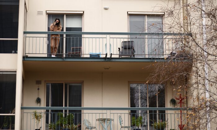 A person speaks on their phone on a balcony of an apartment in Melbourne, Australia, on June 15, 2021. (AAP Image/Daniel Pockett)