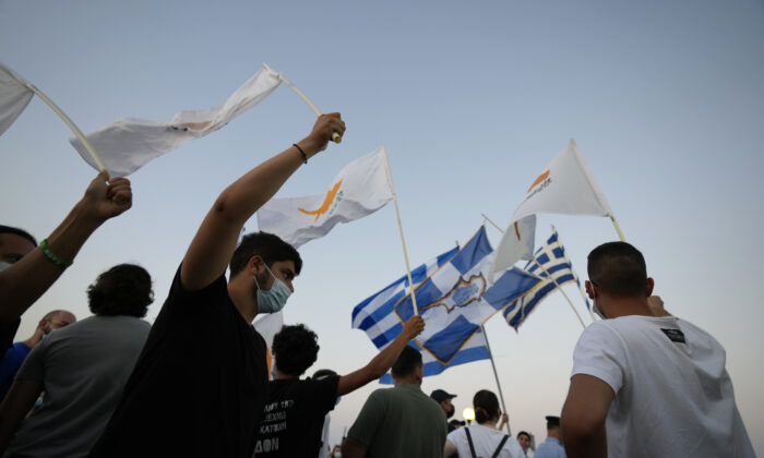 Residents of Varosha or Famagusta, abandoned city, hold Cyprus and Greek flags during a protest against the Turkish President visiting the Turkish occupied part of the island at the north and the 47th anniversary against the Turkish invasion in the island, in Dherynia, Cyprus, on July 19, 2021. (Petros Karadjias/AP Photo)