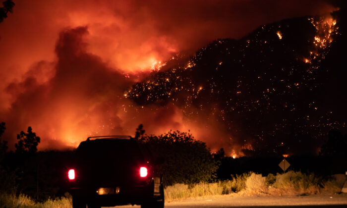 A motorist watches from a pullout on the Trans-Canada Highway as a wildfire burns on the side of a mountain in Lytton, B.C. on July 1, 2021. (The Canadian Press/Darryl Dyck)