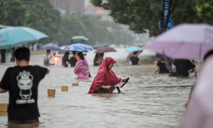 People are wading through floodwaters along a street following heavy rains in Zhengzhou in central China's Henan Province on July 20, 2021. (STR/AFP via Getty Images)