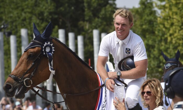 Australia's Jamie Kermond, riding Yandoo Oaks Constellation, receives his trophy after winning the High Jumping event of the second edition of the Longines Paris Eiffel Jumping tournament on the Champ de Mars in Paris on July 3, 2015. (Loic Venance/AFP via Getty Images)