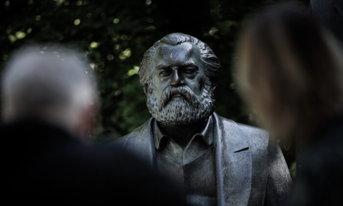 Visitors look at a statue of Karl Marx in a public park in Berlin, Germany, on May 4, 2018. (Sean Gallup/Getty Images)