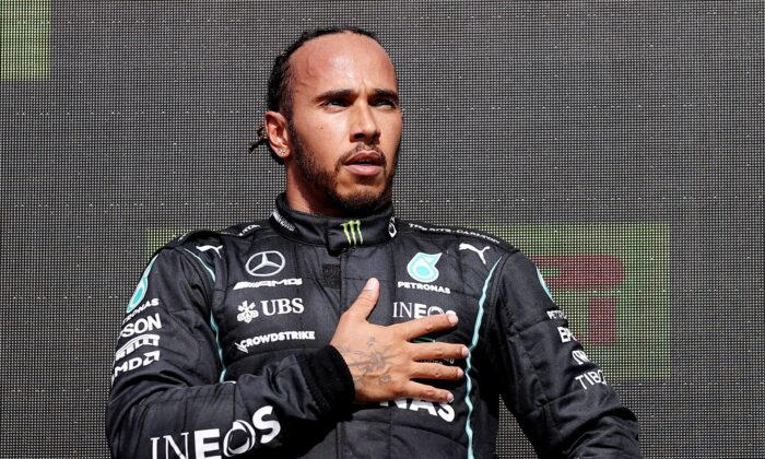 Mercedes' Lewis Hamilton celebrates on the podium after winning the race at British Grand Prix in Silverstone Circuit, Silverstone, Britain on July 18, 2021. (Pool via REUTERS/Lars Baron)