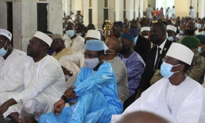 This image taken from video shows Mali's interim president Assimi Goita (C) as he sits with others during Eid al-Adha prayers at The Grande Mosque in Bamako, Mali, on July 20, 2021, before he was attacked by armed men. (Malick Konate/AFP via Getty Images)