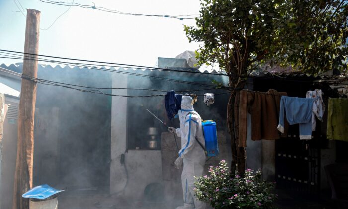A health worker sprays sanitizer outside a house as a precautionary measure against the bird flu in Sola area, on the outskirts of Ahmedabad, India, on March 5, 2021. (Sam Panthaky/AFP via Getty Images)