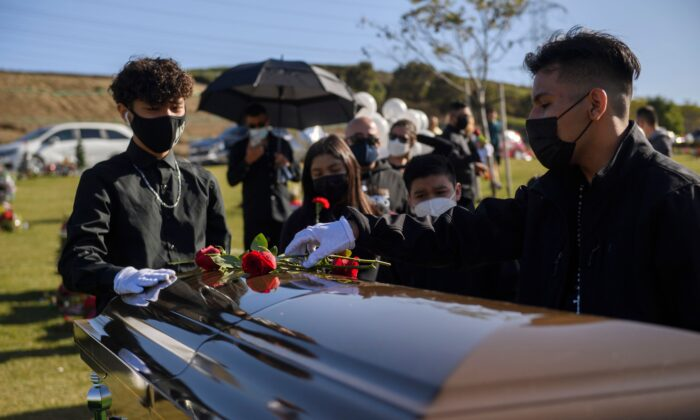 Gilberto Arias, 15, (R) and Javier Dominguez, 13, place flowers on the casket of Gilberto Arreguin Camacho, 58, who died due to COVID-19, during his burial service at a cemetery in Whittier, Calif., on Dec. 31, 2020. (Patrick T. Fallon/AFP via Getty Images)