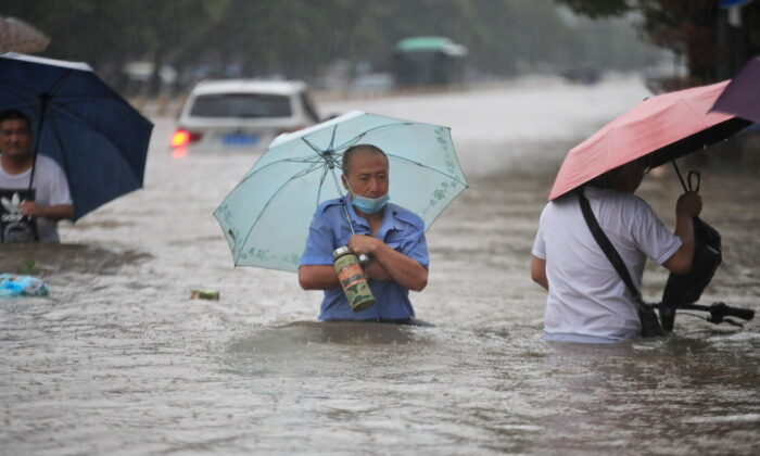 Residents wade through floodwaters on a flooded road in Zhengzhou, Henan province, China, on July 20, 2021. (China Daily via Reuters)