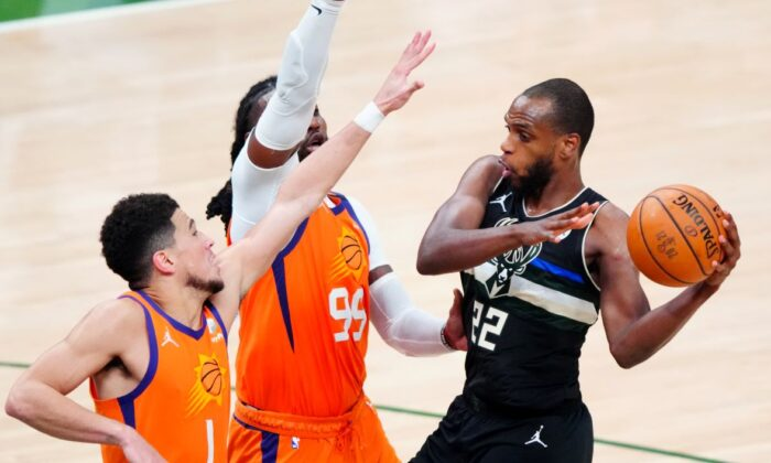 Milwaukee Bucks forward Khris Middleton (22) defended by Phoenix Suns forward Jae Crowder (99) and guard Devin Booker (1) during game six of the 2021 NBA Finals at Fiserv Forum on Jul 20, 2021. (Mark J. Rebilas-USA TODAY Sports)