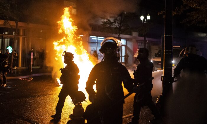 Portland police officers walk past a fire started by a Molotov cocktail that a rioter hurled at them, in Portland, Ore., on Sept. 23, 2020. (Nathan Howard/Getty Images)