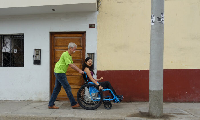 Free Wheelchair Mission founder Don Schoendorfer pushes a woman along a sidewalk. (Courtey of Don Schoendorfer)