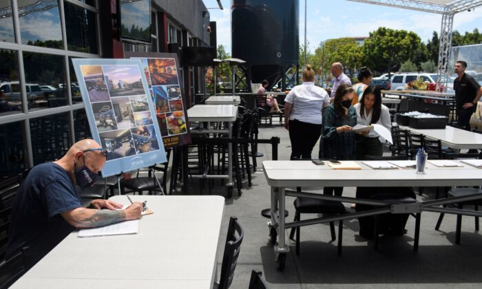 A man completes a job application before interviewing during a Zislis Group job fair at The Brew Hall in Torrance, Calif., on June 23, 2021. (Patrick T. Fallon/AFP via Getty Images)