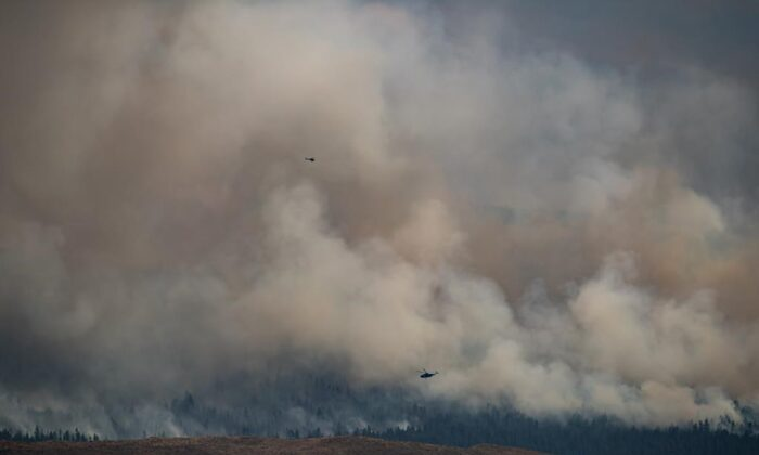 Helicopters fly past the Tremont Creek wildfire as it burns on the mountains above Ashcroft, B.C., on July 16, 2021. (The Canadian Press/Darryl Dyck)
