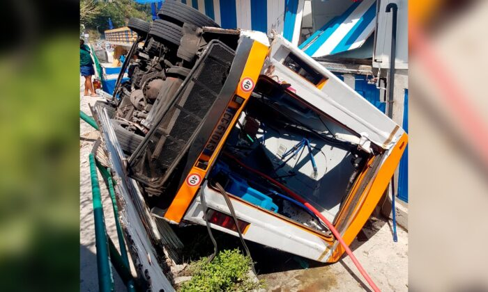 A bus lies on its side after crashing through a guardrail, on the island of Capri, Italy, on Thursday, July 22, 2021. (Italian Firefighters via AP)