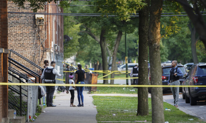 Police investigate the scene of a shooting near 1324 S Christiana Ave in Chicago's Lawndale neighborhood, on July 21, 2021. (Anthony Vazquez/Chicago Sun-Times via AP)