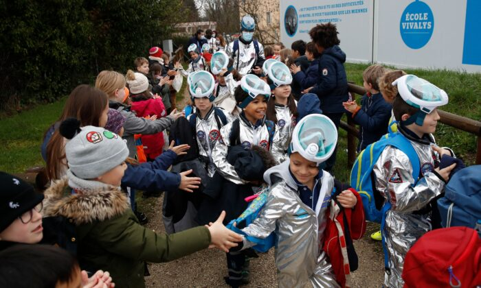 Children shake hands with pupils of the Ecole Vivalys elementary school, wearing spacesuits costumes, as they leave school during their project Mission to Mars in Lausanne, Switzerland, on March 17, 2021. (Stefan Wermuth/AFP via Getty Images)